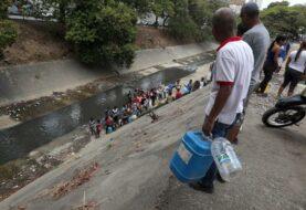 Caraqueños recogen agua en el río Guaire por el apagón